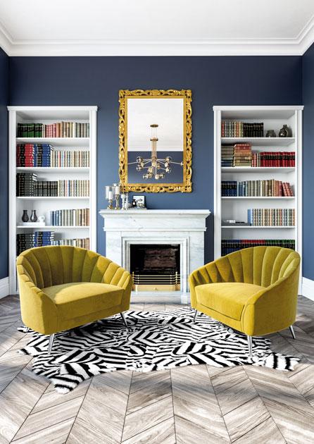 Descrição da Imagem: Cadeirões amarelos de veludo em canto de leitura de escritório.