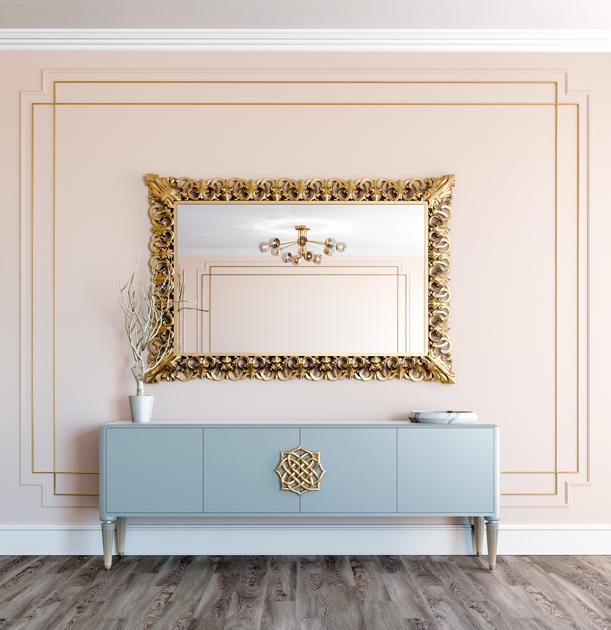 Descrição da imagem: espelho decorativo em talha dourada, por cima de aparador azul claro.