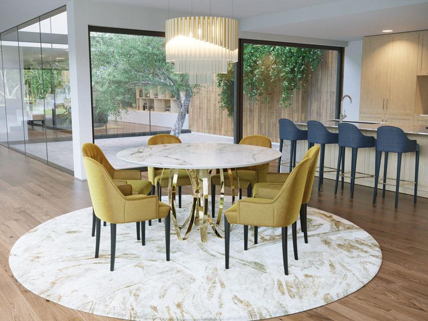 Descrição da imagem: Mesa de jantar redonda com base em inox dourado e tampo em cerâmica tipo mármore.