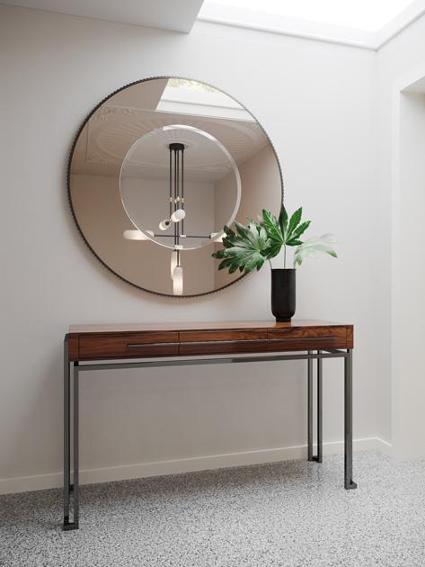 Descrição da imagem: Espelho decorativo redondo com duas tonalidades e consola em madeira e inox.