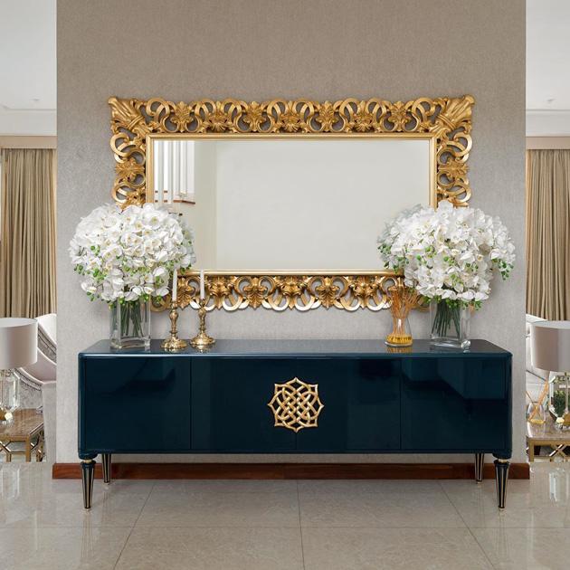 Descrição da Imagem: Espelho decorativo horizontal em talha dourada por cima de aparador azul.