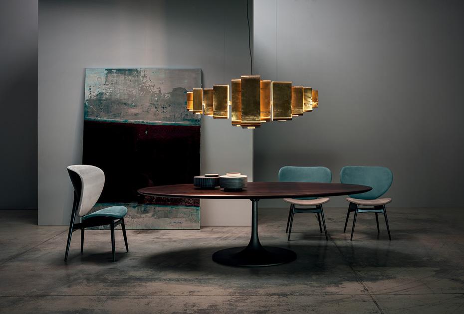 Descrição da Imagem: Cadeira para sala de jantar em pele da marca Baxter, modelo Alma com mesa de jantar, candeeiro e arte.