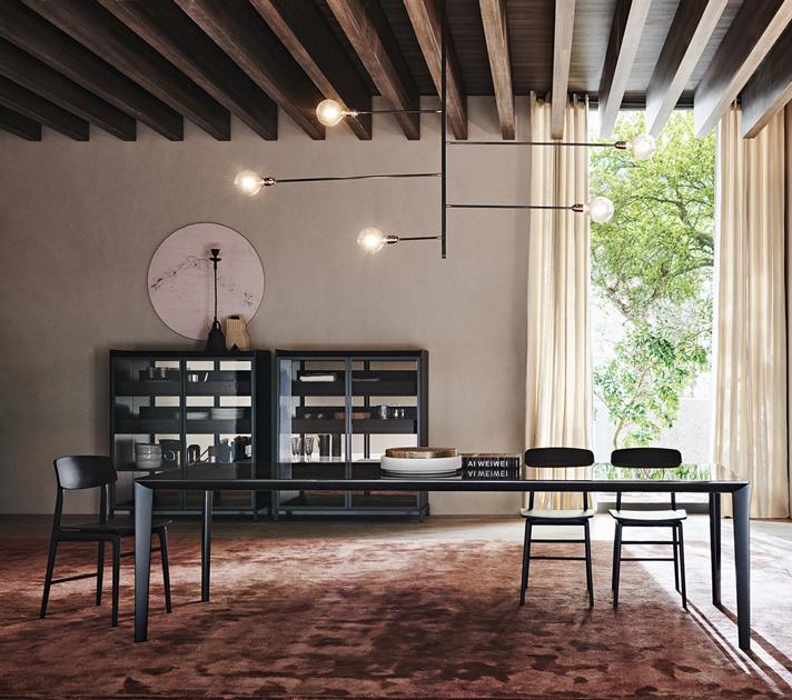 Descrição da Imagem: Cadeira para sala de jantar rústica da marca Molteni, modelo Woody com mesa de jantar e estante atrás.