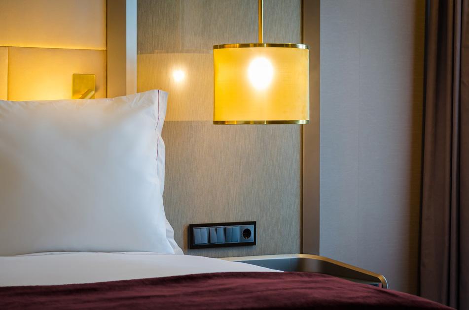 Image description: lighting detail above the bedside table in a hotel bedroom