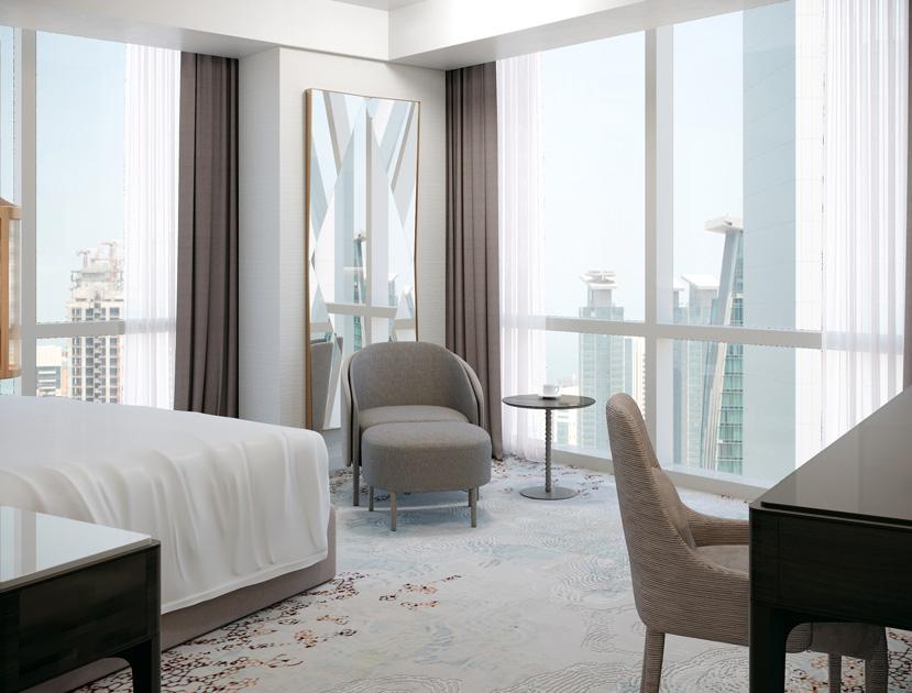 Descrição da imagem: canto de leitura com cadeirão, pousa-pés e mesa de apoio em quarto de hotel